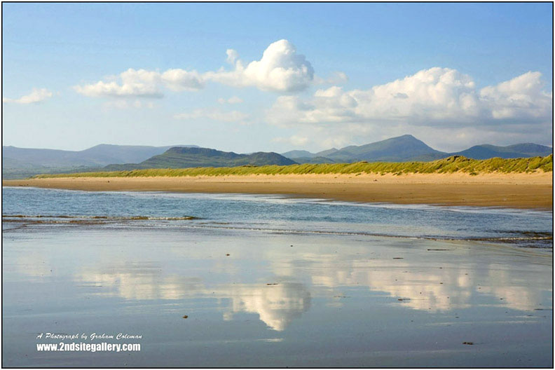 A view from Harlech Beach looking at the distant mountains of Snowdonia with big white clouds in the sky and a mirror reflection in the shallow waters