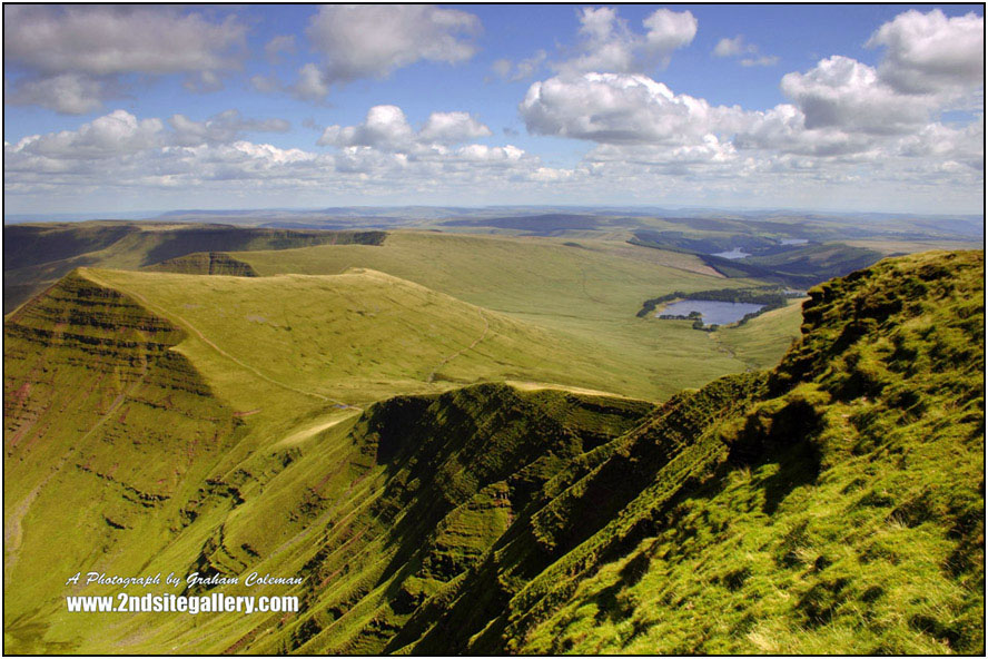View from Pen y fan, The highest point in the Brecon Beacon mountains of South Wales, with a dramatic blue sky and numerous white fluffy clouds, looki