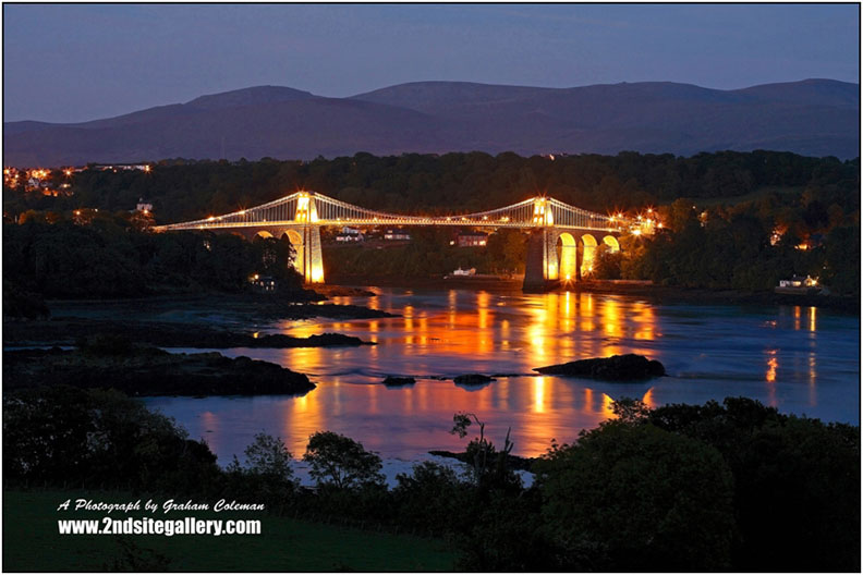 Reflections of The Menai Bridge illuminated in evening light, Thomas Telford's bridge across the menai straits linking Anglesey to mainland North Wale