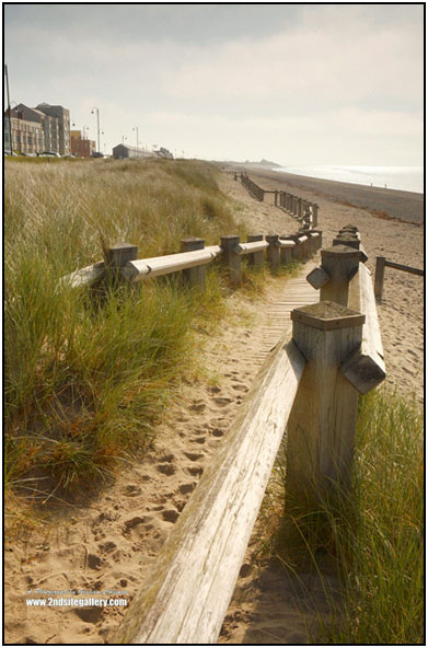 A parthway onto the beach at pwllheli, with wooden ralings through the marram grass and onto the sand