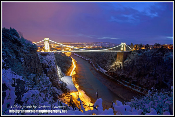 Clifton Suspension Bridge and Avon Gorge in the snow at Twilight, a view of the bridge illuminated with traffic trails on the Portway. An original pho